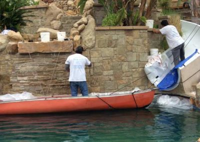 Alex Stone and Tile Services Team Cleaning a Stone Pool Wall